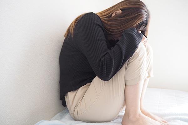 膝を抱える女性